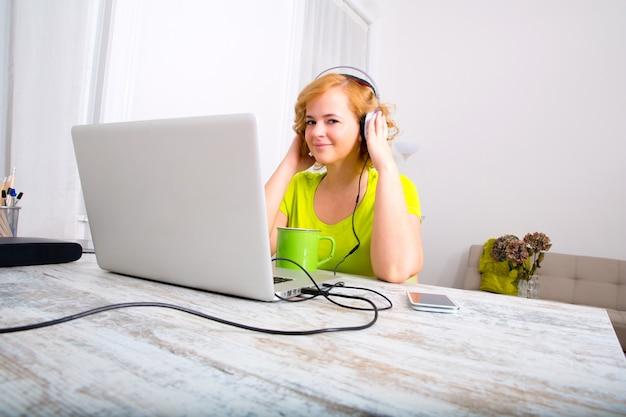 Mujer adulta joven con auriculares delante de un ordenador portátil