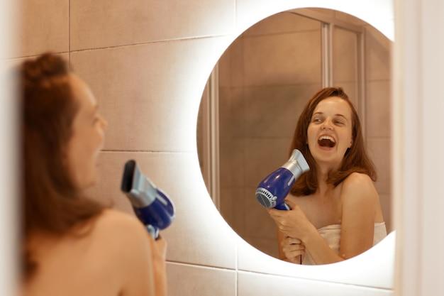 Mujer adulta joven feliz positiva secando el cabello en el baño con secador de pelo, mirando el reflejo en el espejo y cantando, mantiene la boca abierta, procedimientos matutinos.