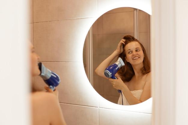 Mujer adulta joven feliz positiva secando el cabello en el baño, sosteniendo el secador de pelo en las manos, mirando sonriendo al reflejo en el espejo, procedimientos matutinos después de tomar la ducha.
