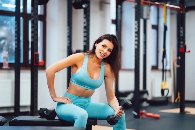 Mujer adulta joven haciendo ejercicios de fuerza en el gimnasio