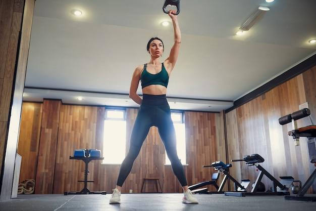 Mujer adulta joven haciendo ejercicios de swing con pesas rusas como parte de un entrenamiento físico