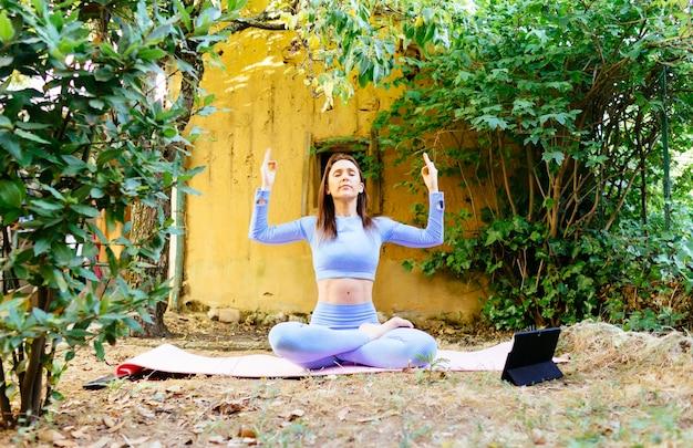 Mujer adulta joven en el jardín de su casa meditando.yoga