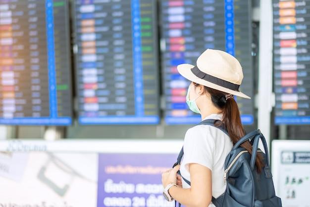 Mujer adulta joven con mascarilla quirúrgica en la terminal del aeropuerto, protección contra la infección por coronavirus (covid-19), viajera asiática con sombrero listo para viajar nuevo concepto de burbuja de viaje y normal