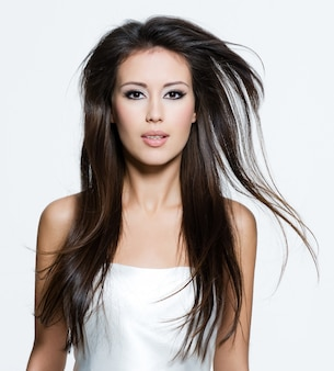 Mujer adulta joven morena con hermosos pelos largos y castaños, posando aislado en blanco