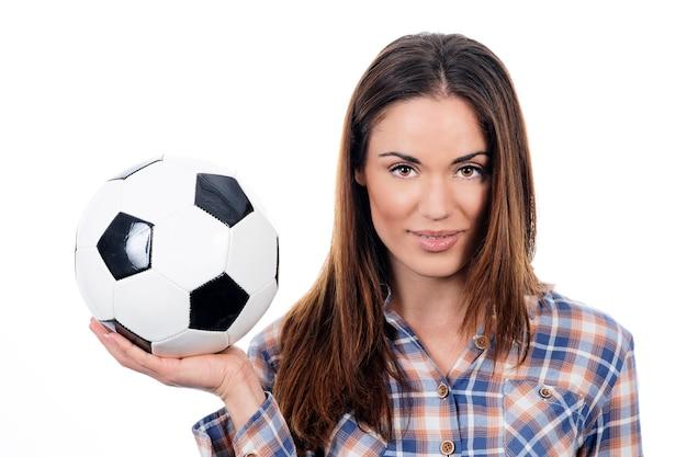 Mujer adulta joven con pelota sobre fondo blanco.