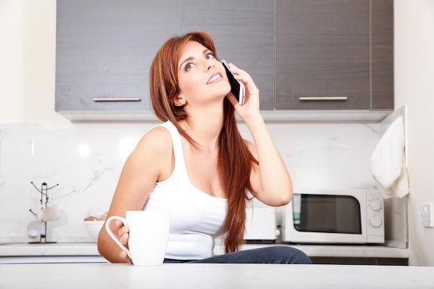 Una mujer adulta joven sentada en la cocina mientras habla por un teléfono inteligente.