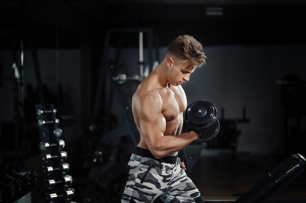 Mujer adulta joven trabajando en el gimnasio, haciendo flexiones de bíceps con la ayuda de su entrenador personal