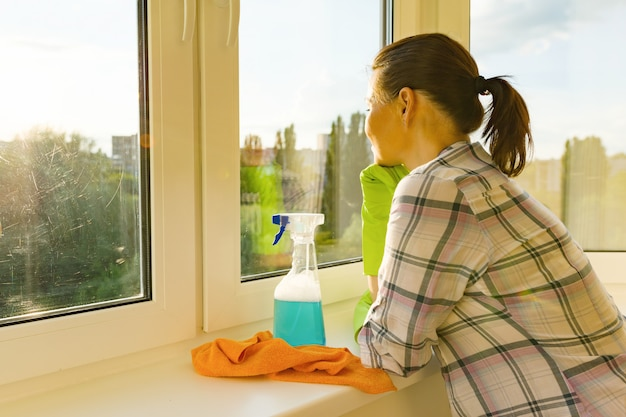 Mujer adulta lava ventanas, limpia la casa