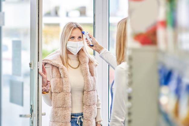 Mujer adulta en máscara médica sometidos a procedimiento covid-19 antes de entrar en la tienda de comestibles