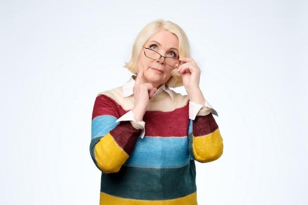 Mujer adulta mayor sosteniendo vasos y mirando hacia los lados