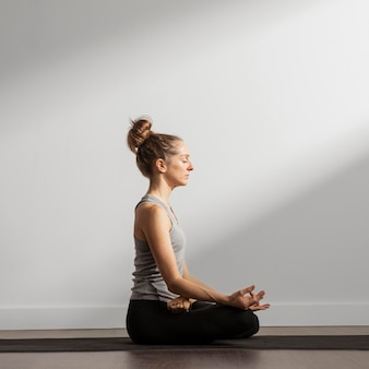 Mujer adulta meditando en casa