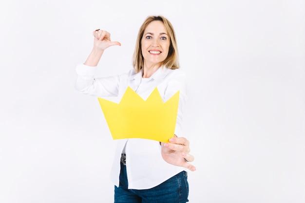 Mujer adulta mostrando corona de papel