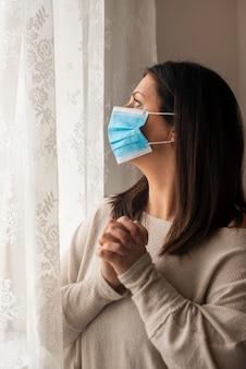Mujer adulta orando por ayuda en casa