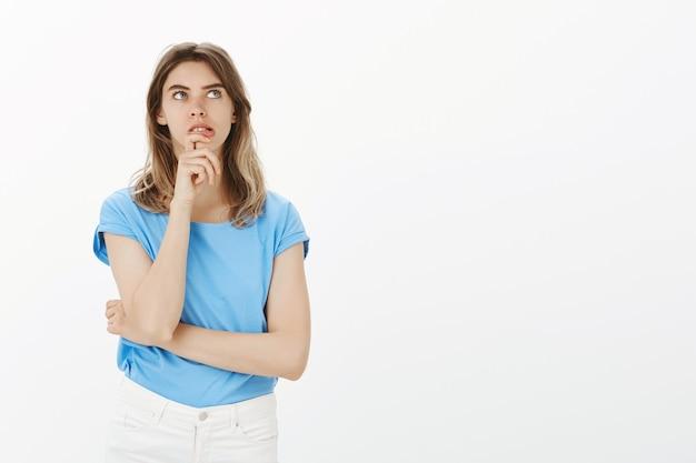Mujer adulta pensativa mirando la esquina superior derecha, pensando, haciendo un plan