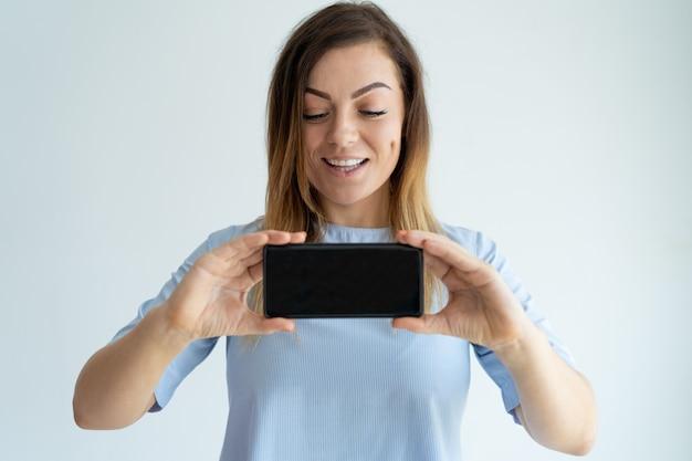 Mujer adulta positiva que muestra la pantalla del teléfono inteligente. lady anunciando algo.
