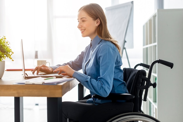 Mujer adulta positiva que trabaja en la oficina