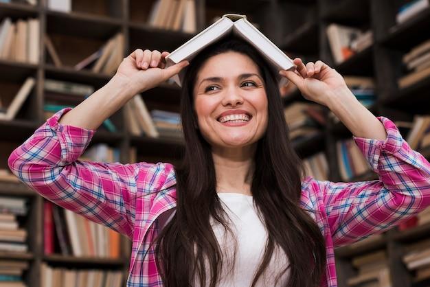 Mujer adulta positiva sonriendo en la biblioteca