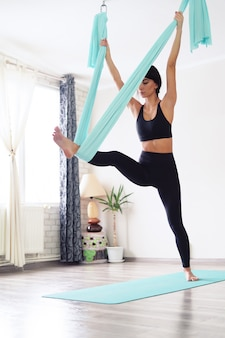 Mujer adulta practica yoga antigravedad