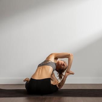 Mujer adulta practicando yoga en casa