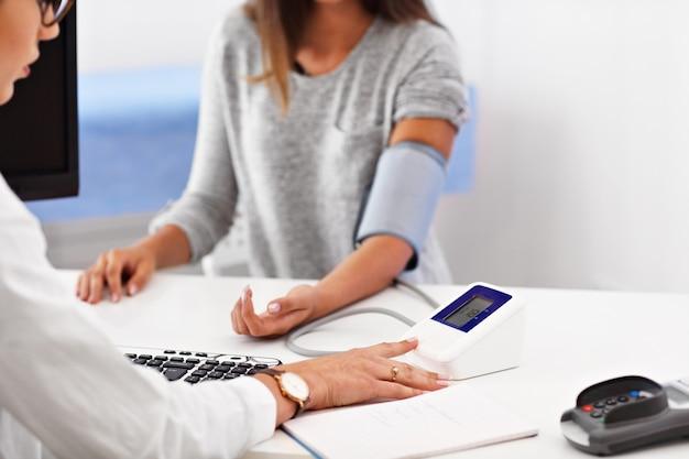 Mujer adulta con prueba de presión arterial durante la visita al consultorio de la doctora