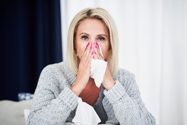 Mujer adulta que se siente indispuesta y sufre de gripe en casa