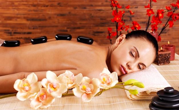 Mujer adulta relajante en el salón de spa con piedras calientes en la espalda. terapia de tratamientos de belleza
