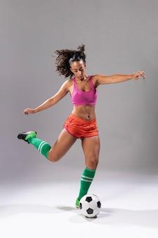 Mujer adulta en ropa deportiva con balón de fútbol