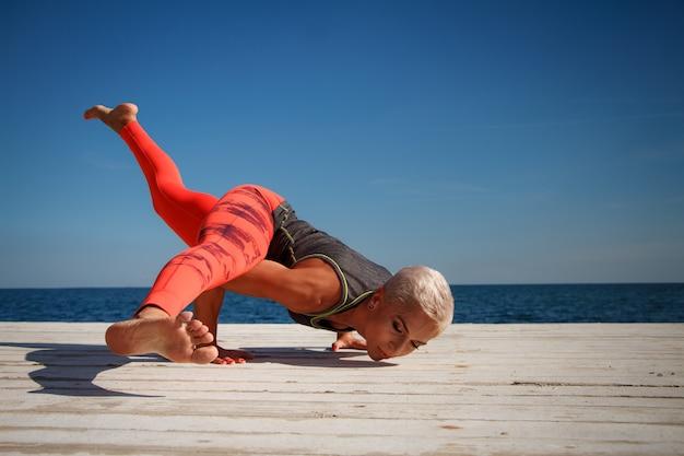 Mujer adulta rubia con corte de pelo corto practica yoga en el muelle contra el fondo del mar y el cielo azul
