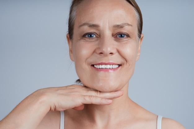 Una mujer adulta sonriente se toca la barbilla con la palma, aplica una crema efecto lifting.