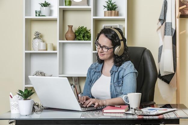 Mujer adulta teletrabajando en la oficina en casa
