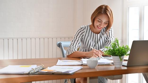 Mujer adulta trabajando con tableta digital y pluma.