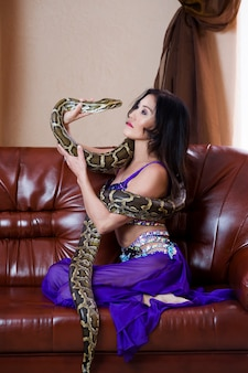 Mujer adulta en traje azul se realiza con gran serpiente