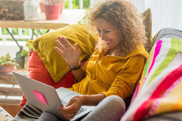 Mujer adulta en videollamada usa computadora portátil sentada en el sofá en casa sonriendo y hablando con amigos o padres: tecnología de comunicación de conexión inalámbrica y gente moderna en el interior