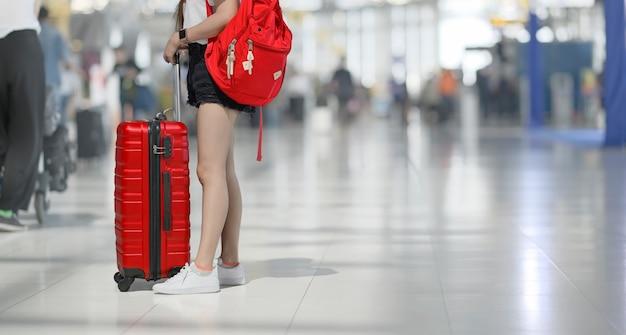 Mujer en el aeropuerto con equipaje rojo