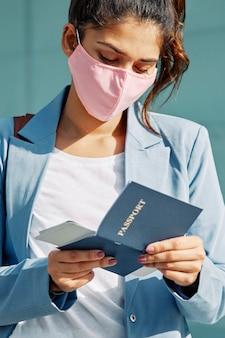Mujer en el aeropuerto con máscara médica comprobando su pasaporte