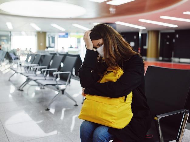 Mujer en el aeropuerto sosteniendo su cabeza máscara médica esperando