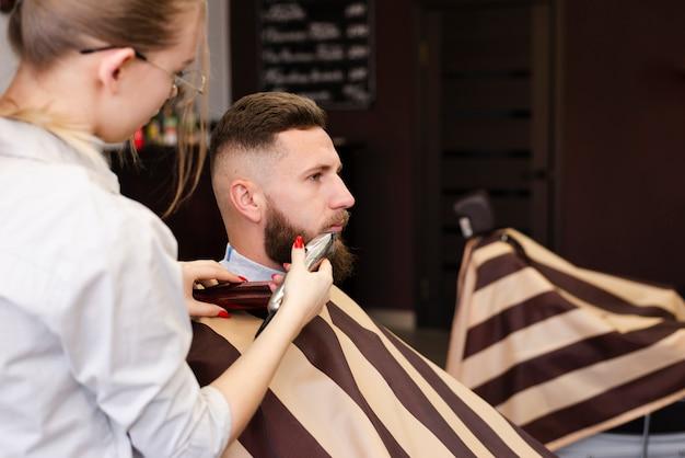 Mujer afeitarse la barba de su cliente con espacio de copia