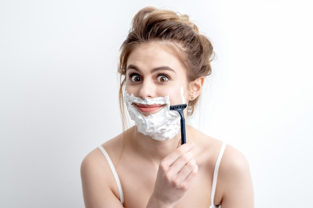 Mujer afeitarse la cara por la maquinilla de afeitar