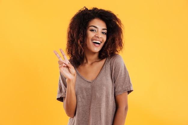 Mujer africana alegre que muestra el signo de la paz