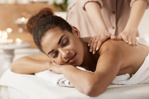 Mujer africana atractiva que tiene masaje que se relaja en salón del balneario. ojos cerrados.