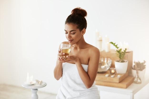 Mujer africana bebiendo té verde descansando en el salón de spa.