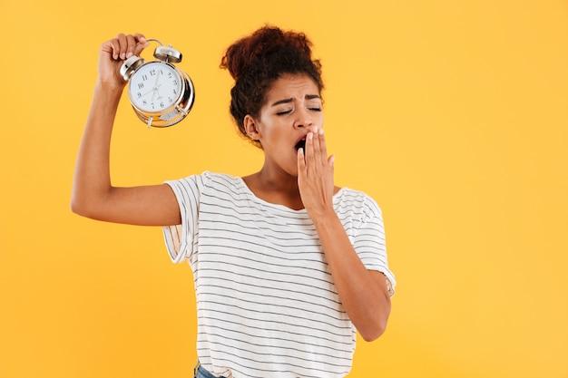 Mujer africana cansada bosteza y sostiene despertador