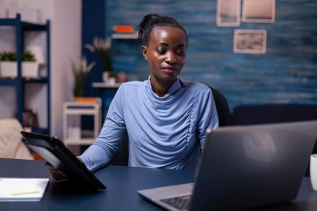 Mujer africana concentrada trabajando en fecha límite con tablet pc y computadora portátil en la oficina en casa a altas horas de la noche. empleado enfocado ocupado que usa la red inalámbrica de tecnología moderna haciendo horas extras escribiendo.