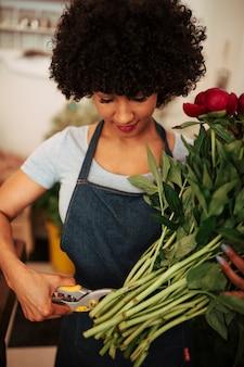 Mujer africana, corte, tallo, de, flores rojas, con, tijeras de podar