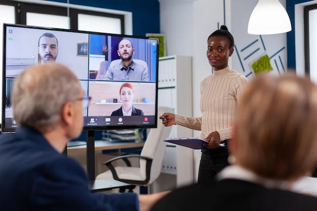 Mujer africana discutiendo con administradores remotos en videollamada presentando nuevos socios en webcam. la gente de negocios que habla con la cámara web, la conferencia en línea participa en la lluvia de ideas de internet, la oficina a distancia