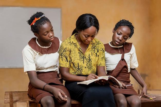 Mujer africana enseñando a los niños en clase