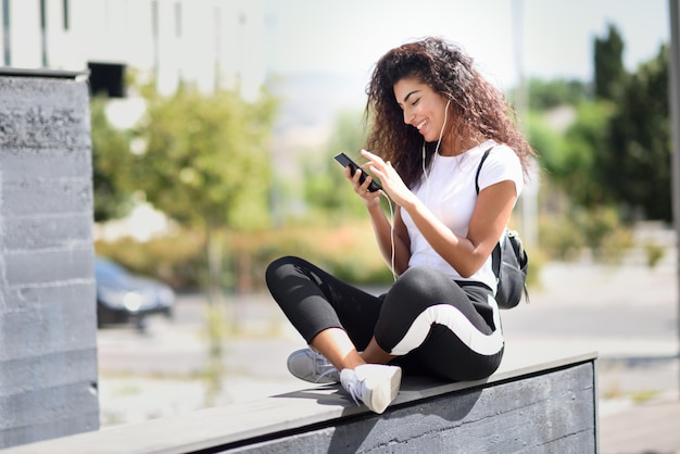 Mujer africana escuchando música con auriculares y teléfono inteligente