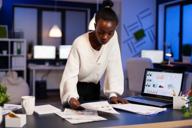 Mujer africana estresada que trabaja con documentos financieros de pie en el escritorio revisando gráficos, sosteniendo papeles, leyendo informes a altas horas de la noche en la oficina de puesta en marcha haciendo horas extras para respetar el plazo