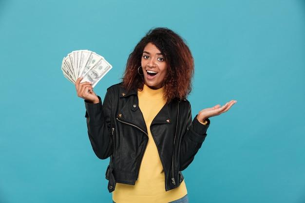 Mujer africana feliz sorprendida en chaqueta de cuero con dinero