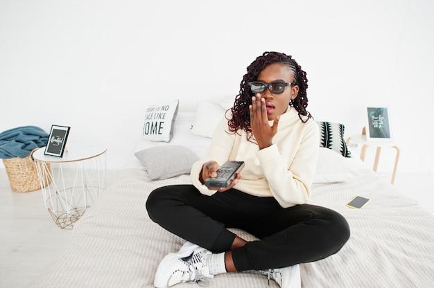 Mujer africana en gafas 3d viendo la televisión en casa y sosteniendo un control remoto en la cama